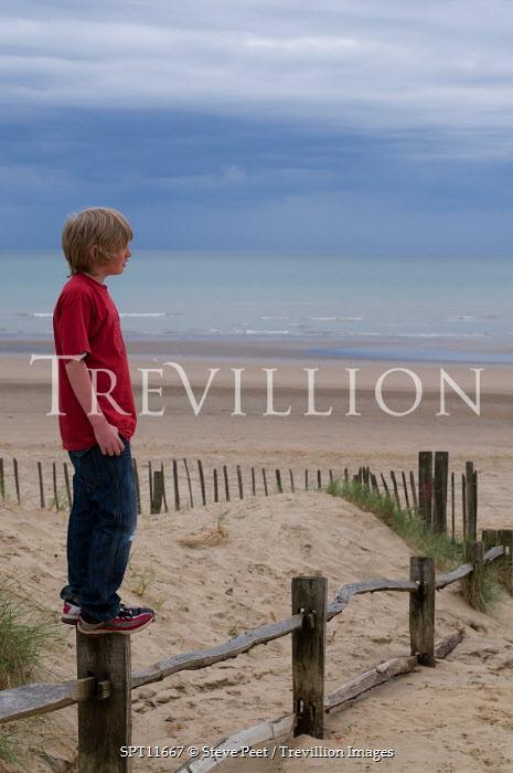 Steve Peet BOY STANDING ON POST ON BEACH Women