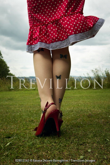 Emma Delves-Broughton RETRO WOMAN WEARING RED SKIRT AND HEELS IN FIELD Women