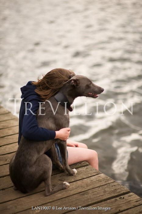 Lee Avison GIRL HUGGING DOG ON JETTY Children