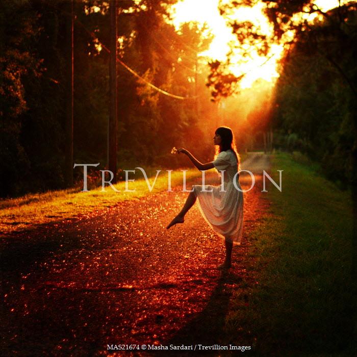 Masha Sardari WOMAN DANCING ON ROAD IN SUNSET Women