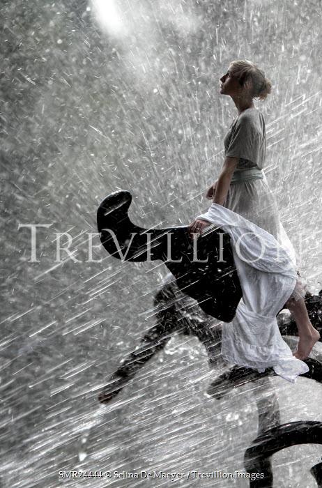 Selina De Maeyer WOMAN STANDING ON SCULPTURE IN RAIN Women
