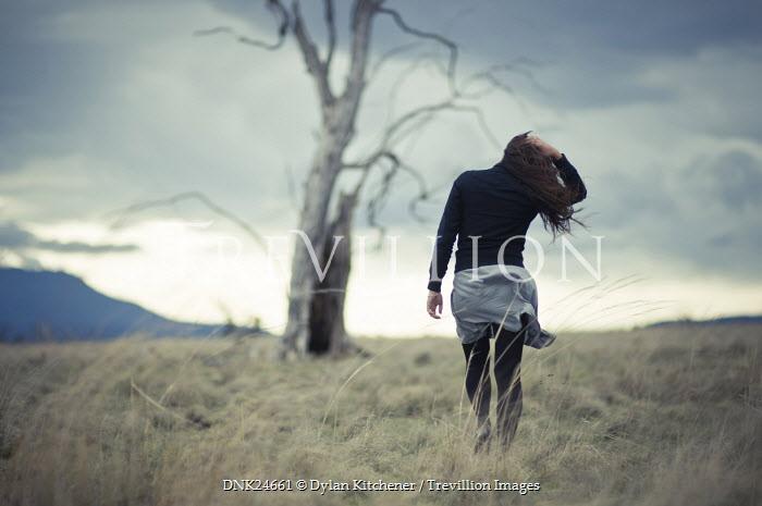 Dylan Kitchener WOMAN WALKING IN WINTRY FIELD WITH TREE Women