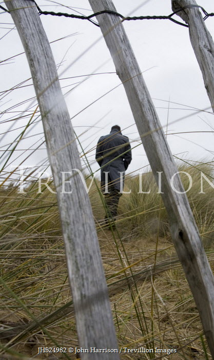 John Harrison MAN WALKING IN SAND DUNE WITH FENCE Men