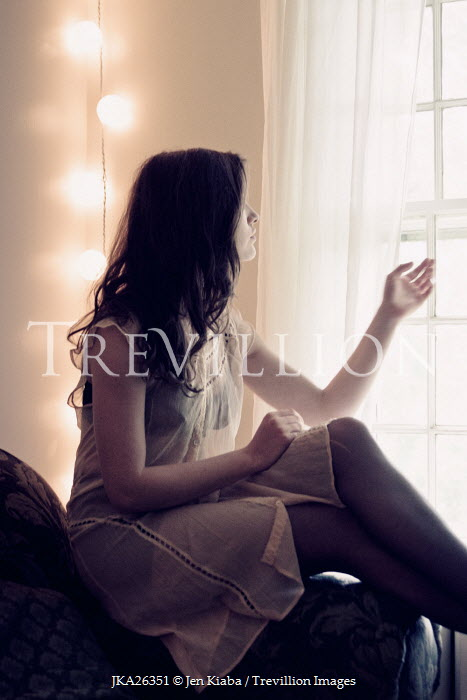 Jen Kiaba WOMAN SITTING BY WINDOW WITH LIGHTS Women