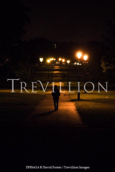 David Foster MAN WALKING THROUGH PARK AT NIGHTTIME Men