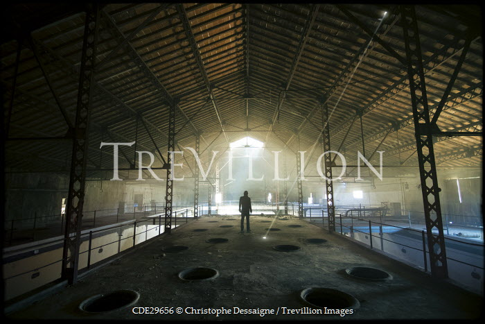 Christophe Dessaigne SILHOUETTED MAN IN INDUSTRIAL BUILDING Men