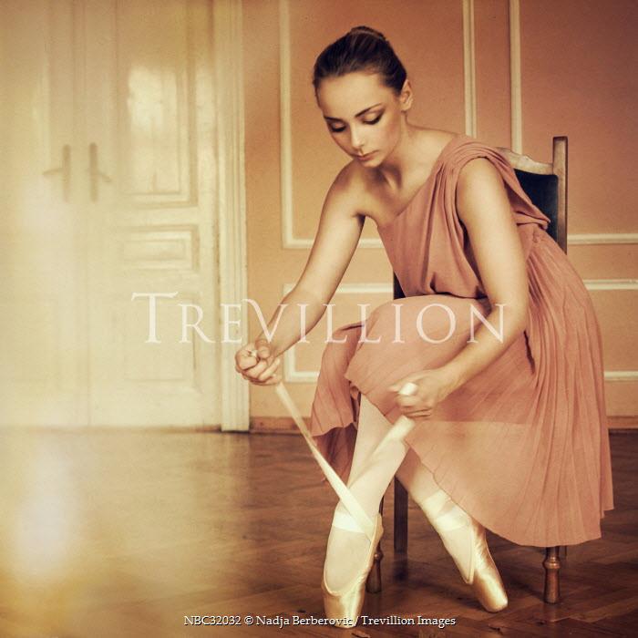 Nadja Berberovic WOMAN TYING BALLET SHOES INDOORS Women