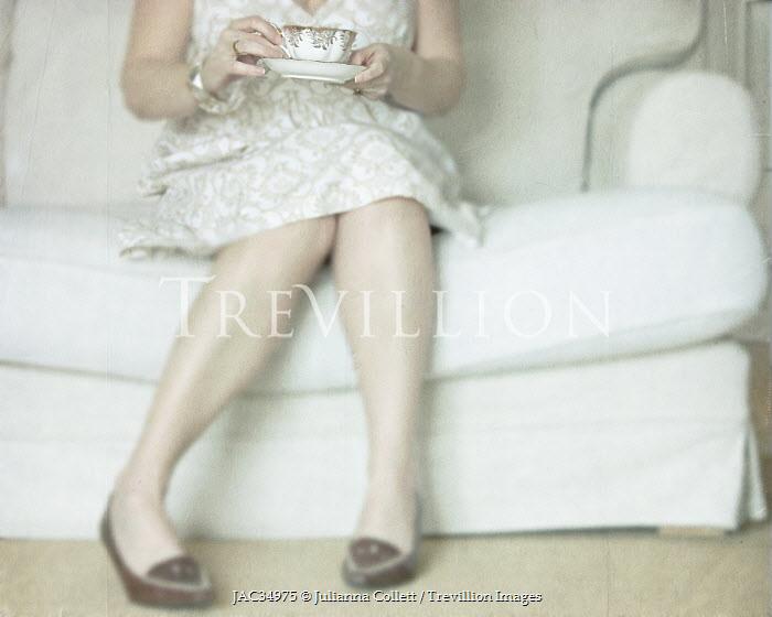 Julianna Collett WOMAN DRINKING TEA ON SOFA Women