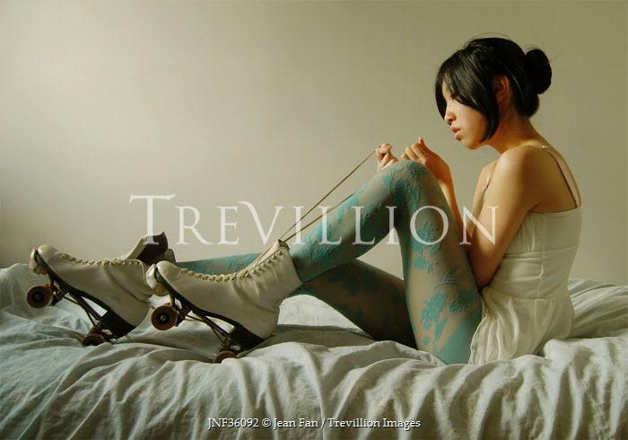 Jean Fan WOMAN WITH ROLLER SKATES ON BED Women