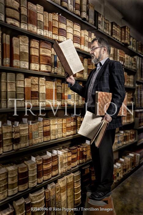 Reto Puppetti MAN READING BOOKS IN LIBRARY Men