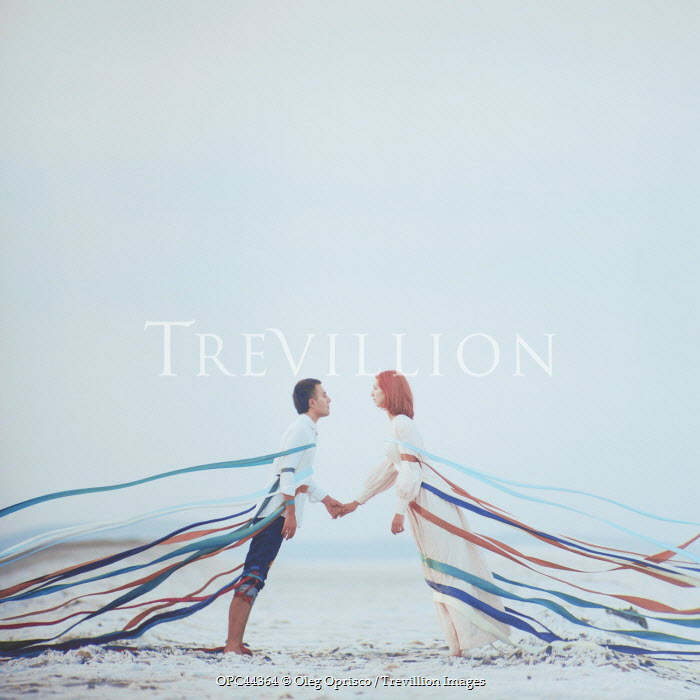Oleg Oprisco COUPLE HOLDING HAND ON BEACH WITH RIBBONS Couples
