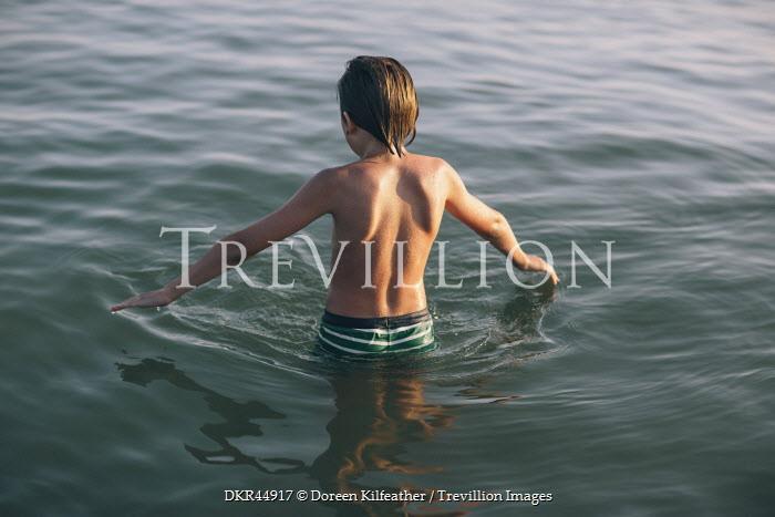Doreen Kilfeather BOY IN TRUNKS STANDING IN SEA Men