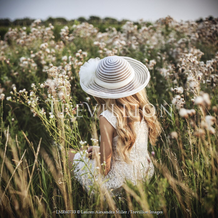 Lauren Alexandra Miller WOMAN SITTING IN FIELD WEARING WHITE HAT Women