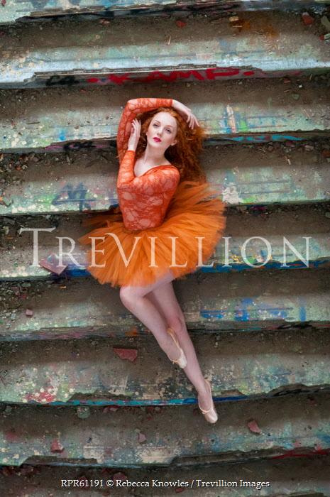 Rebecca Knowles BALLERINA WEARING ORANGE LYING ON STEPS Women
