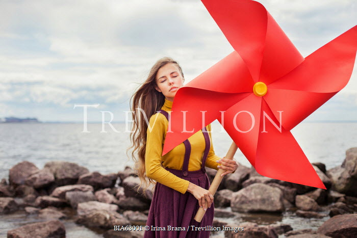 Irina Brana SURREAL WOMAN WITH LARGE WINDMILL TOY OUTSIDE Women