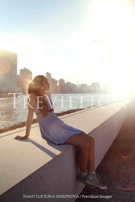 ILINA SIMEONOVA WOMAN SITTING ON WALL NEAR SKYSCRAPERS Women