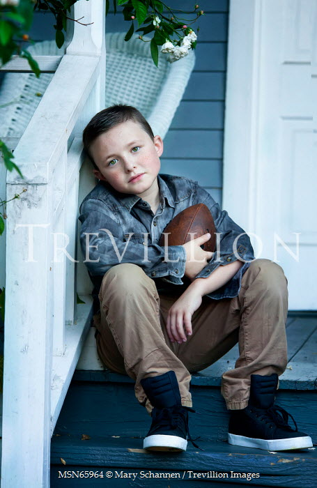 Mary Schannen BOY SITTING HOLDING AMERICAN FOOTBALL Children