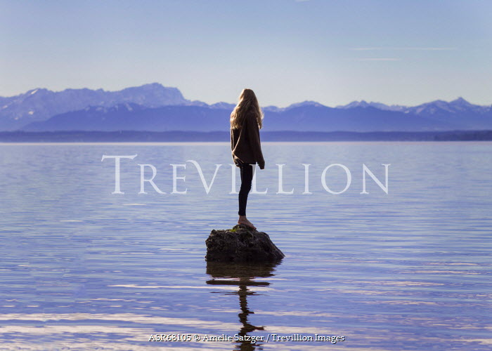 Amelie Satzger YOUNG WOMAN STANDING ON ROCK IN LAKE Women