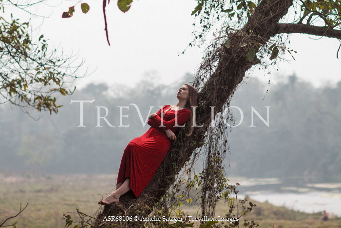 Amelie Satzger YOUNG WOMAN LYING ON SLANTED TREE Women