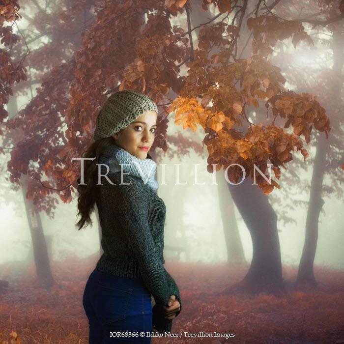 Ildiko Neer WOMAN STANDING IN AUTUMNAL FOREST Women
