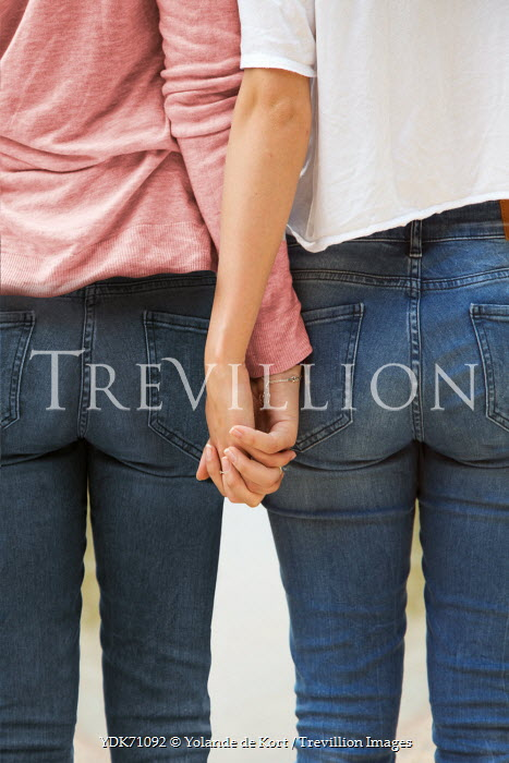 Yolande de Kort TWO WOMEN IN JEANS HOLDING HANDS Couples