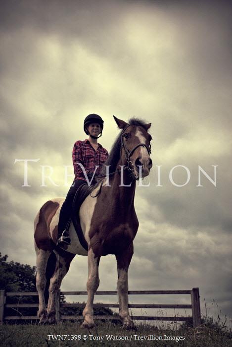 Tony Watson YOUNG WOMAN RIDING HORSE IN COUNTRYSIDE Women
