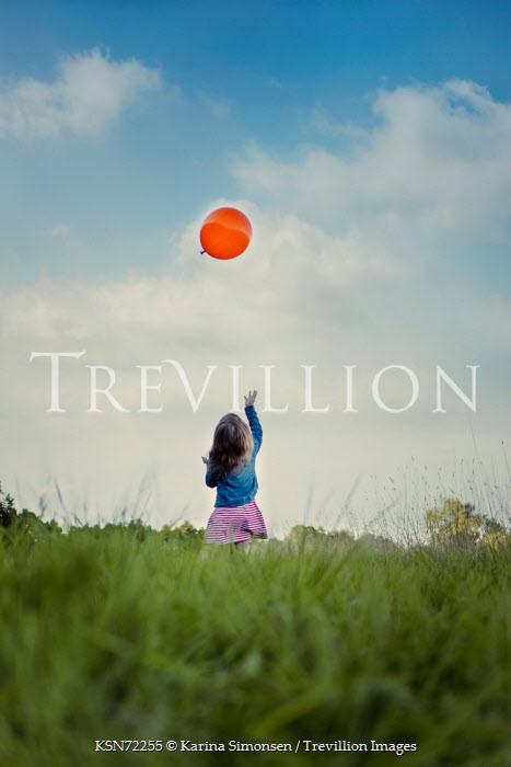 Karina Simonsen GIRL PLAYING WITH BALLOON IN FIELD Children