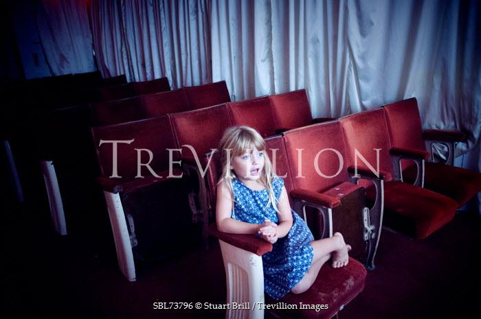 Stuart Brill LITTLE BLONDE GIRL SITTING IN THEATRE Children