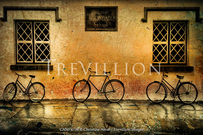 Christine Amat THREE BICYCLES LEANED ON RUSTIC BUILDING Miscellaneous Transport