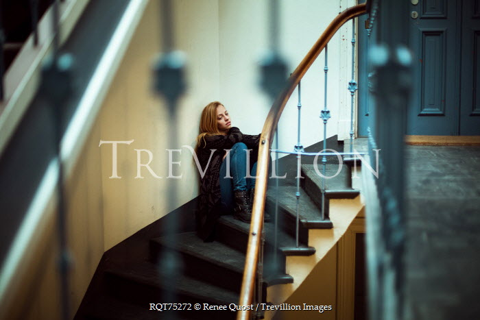 Renee Quost YOUNG BLONDE WOMAN SITTING ON STAIRS IN HALLWAY Women
