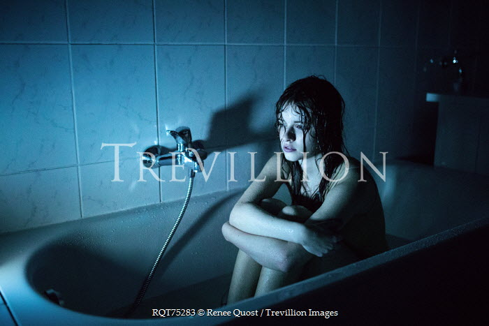 Renee Quost YOUNG WOMAN SITTING IN SHADOWY BATH TUB Women