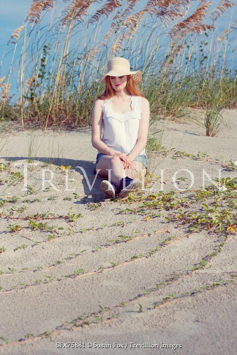 Susan Fox YOUNG WOMAN IN SUNHAT SITTING ON SANDY BEACH Women