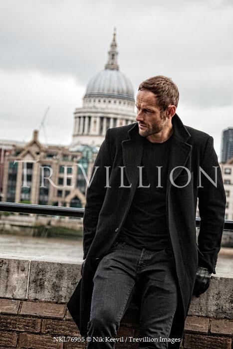 Nik Keevil MAN WEARING BLACK COAT BY LONDON RIVER Men