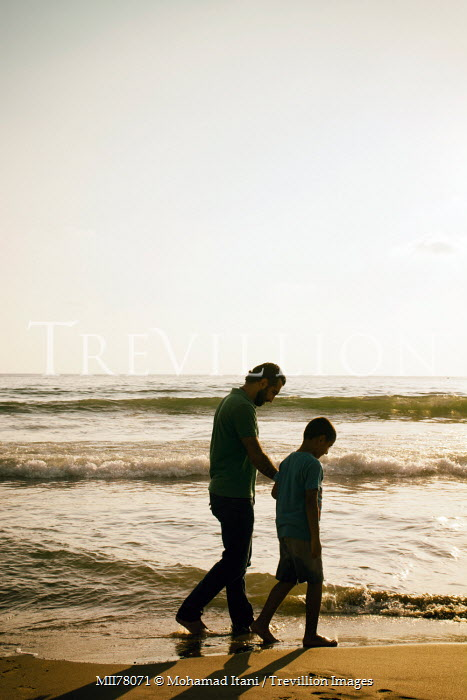 Mohamad Itani FATHER AND SON WALKING ON SANDY BEACH Groups/Crowds