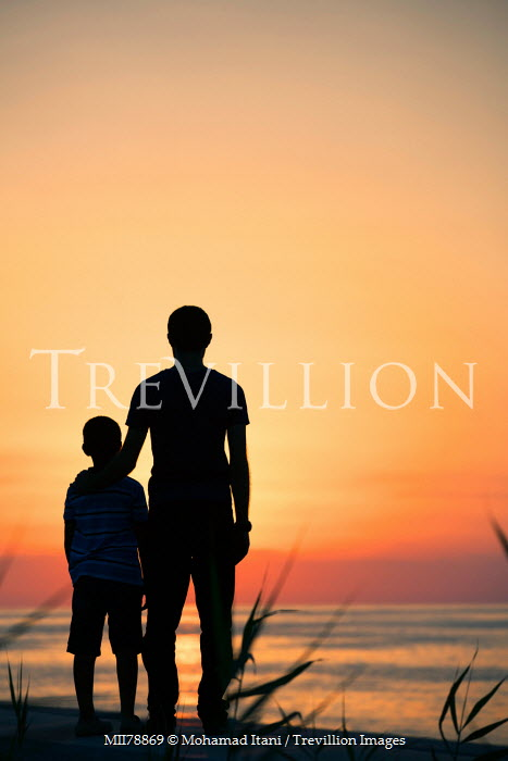 Mohamad Itani SILHOUETTE OF FATHER AND SON BY SEA AT SUNSET Groups/Crowds