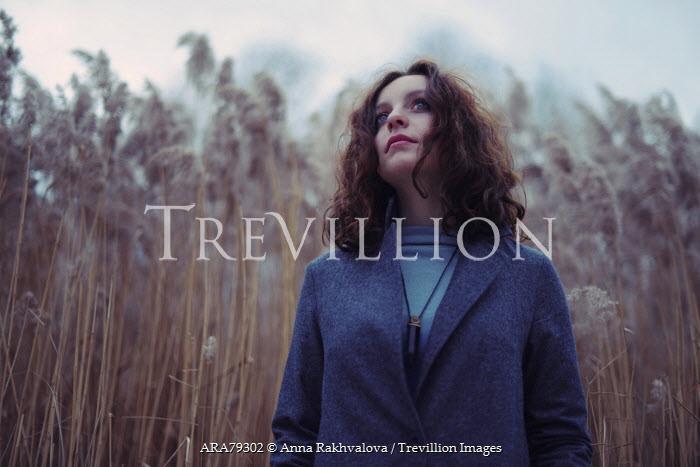 Anna Rakhvalova BRUNETTE WOMAN WEARING COAT IN LONG GRASS Women