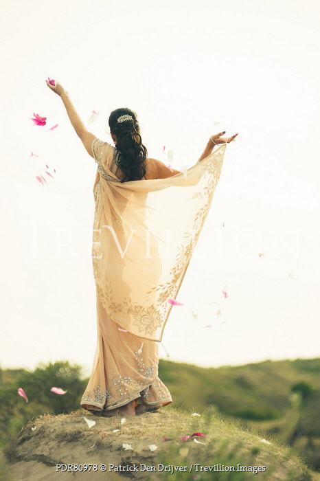 Patrick Den Drijver INDIAN WOMAN IN SARI SCATTERING FLOWER PETALS Women