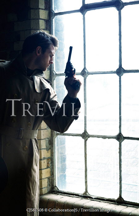 CollaborationJS man with gun wearing raincoat by window Men