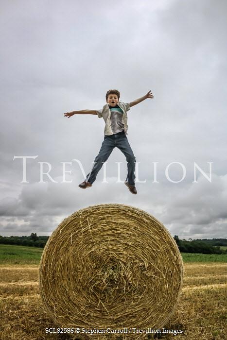 Stephen Carroll BOY JUMPING ON HAY BALE Children