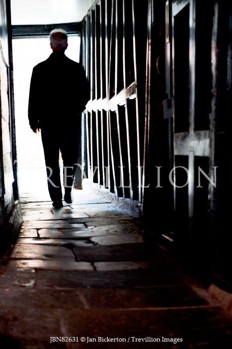 Jan Bickerton Silhouette of man walking down medieval passageway Men