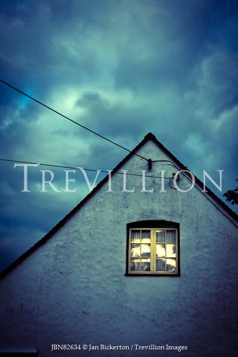 Jan Bickerton lit Window in house under cloudy sky Houses
