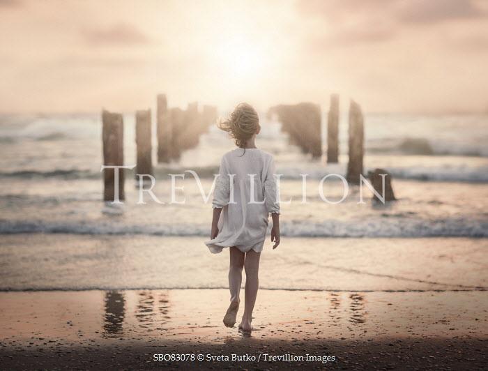 Sveta Butko LITTLE GIRL WALKING ON BREEZY BEACH Children