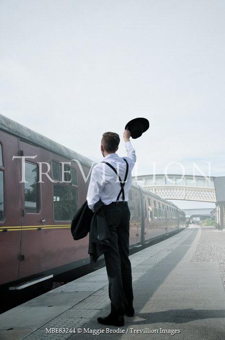 Maggie Brodie RETRO MAN WAVING HAT ON TRAIN PLATFORM Men