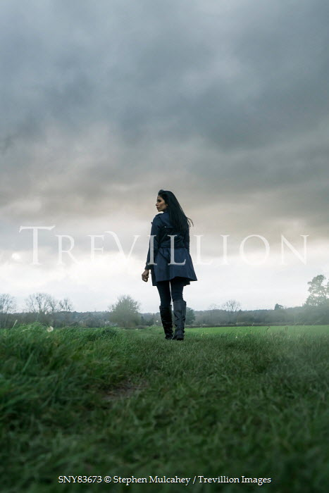 Stephen Mulcahey modern woman walking in cloudy field Women