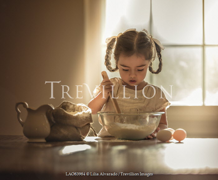 Lilia Alvarado LITTLE GIRL BAKING IN SUNLIT KITCHEN Children