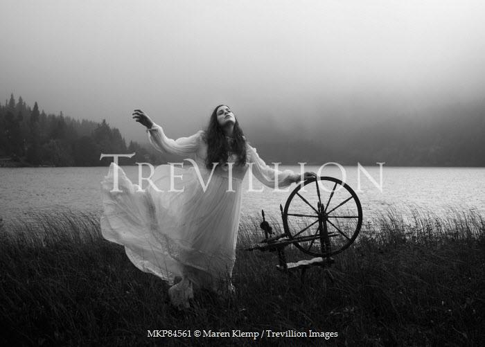 Maren Klemp WOMAN WITH SPINNING WHEEL BY LAKE Women