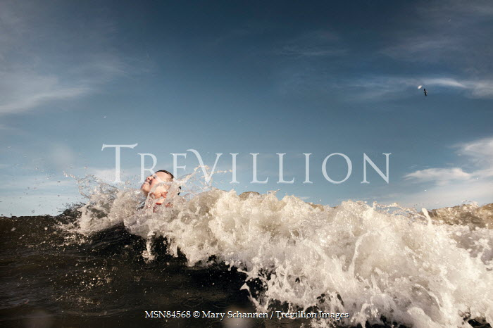 Mary Schannen BOY SWIMMING IN SEA WITH BIG WAVE Children