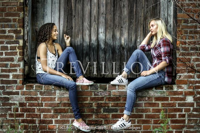 Stephen Carroll TWO TEENAGE GIRLS SITTING ON WALL Women