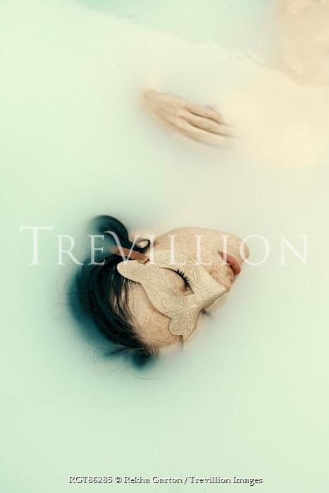 Rekha Garton YOUNG WOMAN IN MASK LYING IN MILKY WATER Women