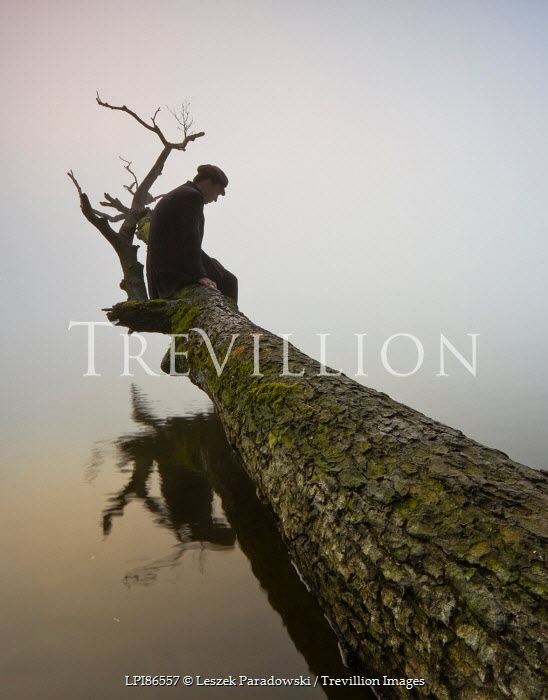 Leszek Paradowski MAN SITTING ON FALLEN TREE ON LAKE Men